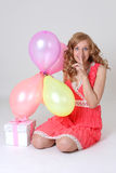 Birthday girl with gift and balloons showing shh Stock Image