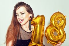 A birthday girl on her 18th birthday with gold number baloons. Excited eighteen girl with green make up and black dress smile. stock photo