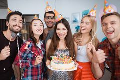 The birthday girl is holding a cake with candles. Girls and guys are standing around her. They are posing for a photo and smiling stock photo