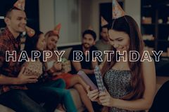 Birthday Girl Open Gift. Happy Birthday Celebration. Friends Happy Together. Guest in Birthday Hat. Guys Sit on Couch. Lively royalty free stock photography