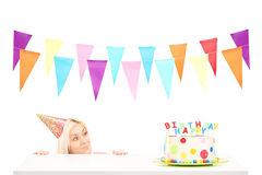 Birthday girl with a party hat looking at a birthday cake Stock Photos