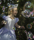 Birthday Girl Princess with Bubbles. A joyful, very happy, smiling, young girl  dressed as a princess in a blue dress and crown, celebrates her birthday by Stock Images