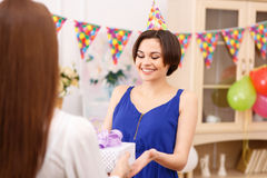 Birthday girl receiving presents. Happy moments. Young cheerful birthday girl is smiling radiantly while receiving birthday gifts from her friends stock photo