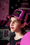 Birthday Girl. A young girl surrounded by pink and black, wears a, Happy Birthday to Me hat.  She is looking off camera with a close lipped smile Royalty Free Stock Images