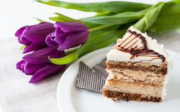 Birthday greetings. A piece of birthday cake and three purple tulips stock images