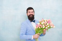 Birthday greetings. Best flowers for girlfriend. Flowers for her. Man bearded suit bow tie hold tulips bouquet. Gentleman making romantic surprise for her stock image