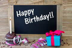 Birthday greetings. On black chalkboard with cupcake and gift box royalty free stock images