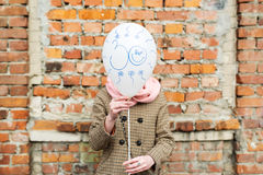 Birthday greetings. Thirty years. The girl costs against brick wall and covers the face with balloon stock photo