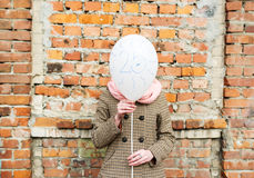 Birthday greetings. Twenty five years. The girl costs against brick wall and covers the face with balloon royalty free stock photos