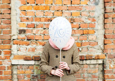 Birthday greetings. Twenty years. The girl costs against brick wall and covers the face with balloon stock photos