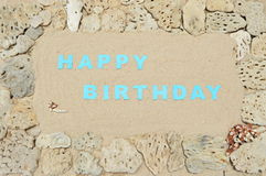 Birthday greetings. Written in a frame of white corals at the beach stock image