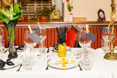 Birthday guests table setting with fresh flowers in black and gold style, indoor.  Stock Images