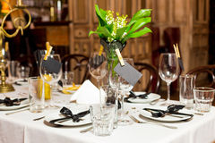 Birthday guests table setting with fresh flowers in black and gold style, indoor Stock Photos