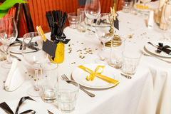 Birthday guests table setting with fresh flowers in black and gold style, indoor.  Stock Photos
