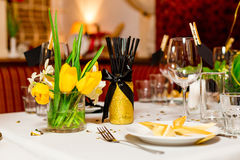 Birthday guests table setting with fresh flowers in black and gold style, indoor Stock Image