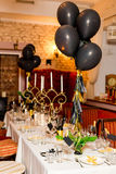 Birthday guests table setting with fresh flowers in black and gold style, indoor Stock Photography