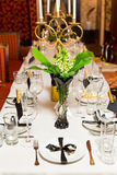 Birthday guests table setting with fresh flowers in black and gold style, indoor Stock Photo