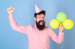 Birthday guy with happy face and big smile on blue background. Bearded man wearing paper cap having fun. Hipster with. Stylish beard and mustache celebrating Royalty Free Stock Photos