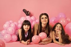 Birthday, happiness, childhood. Family, children, mother with party balloons. Little girls, mom in pink balloons. Mother and kids in balloons, mothers day stock photos