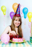 Birthday. Happy attractive girl lights a candle Stock Photo