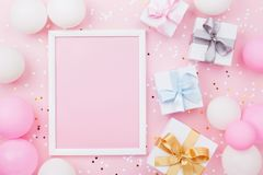 Birthday or holiday mockup with frame, gift box, pastel balloons and confetti on pink table top view. Flat lay composition.