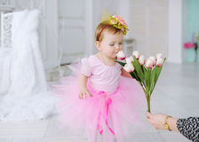 Birthday of the little girl. She smells aroma of tulips royalty free stock photography