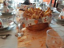 Birthday lunch. Fold a napkin,glasses with a basket of toast on the table Royalty Free Stock Image