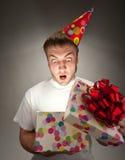 Birthday man opening gift box. Surprised birthday man opening big gift box Stock Photos