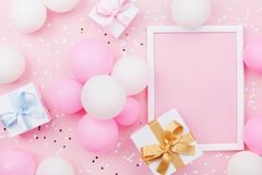 Birthday mockup with frame, gift box, pastel balloons and confetti on pink table top view. Flat lay composition. stock photos