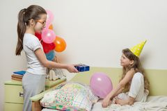 Birthday morning. Older sister giving surprise gift to her cute little sister. Children at home in bed.  royalty free stock photos
