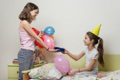 Birthday morning. Older sister giving surprise gift to her cute little sister. Children at home in bed royalty free stock image
