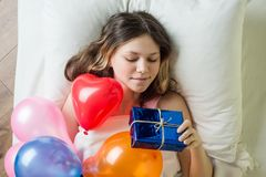 Birthday morning. Teenage girl lying in bed on pillow holding a gift, top view royalty free stock images
