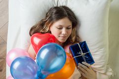 Birthday morning. Teenage girl lying in bed on pillow holding a gift, top view royalty free stock photos