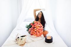 Birthday morning of young woman with huge bouquet of roses and tasty cake