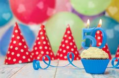 Birthday muffin for 50 anniversary candle. With party hats and balloons Stock Photography