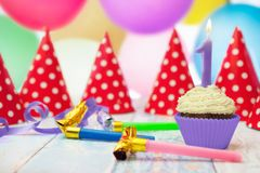 Birthday muffin, birthday blowouts and party hats stock photos