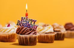 Birthday muffin with candle on yellow background. stock photos