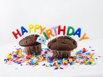 Birthday muffins. Chocolate muffins with candles that spell Happy Birthday Royalty Free Stock Photos