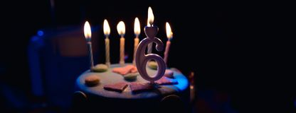 Birthday cake with burning candles and age 6 candle in the dark background with candies in decor stock photography