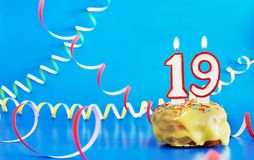 Birthday of nineteen years. Cupcake with white burning candle in the form of number 19. Vivid blue background with copy space royalty free stock image
