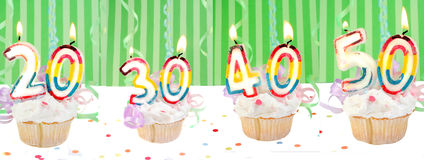 Birthday number cupcakes banner. Celebratory birthday cupcakes with lit candles and numbers like twenty, thirty, forty, and fifty with confetti and green striped Stock Photo