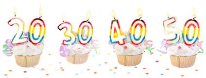 Birthday number cupcakes banner. Celebratory birthday cupcakes with lit candles and numbers like twenty, thirty, forty, and fifty with confetti Stock Photography