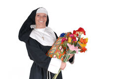 Birthday nun, sister. Middle aged sister, nun with birthday present and flowers. Happy expression on face, big smile royalty free stock photography