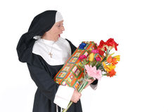 Birthday nun, sister. Middle aged sister, nun with birthday present and flowers, happy, surprised expression on face stock images