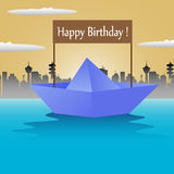 Birthday paper boat. Abstract colorful background with a blue paper boat with the text Happy Birthday floating on the water Stock Image