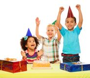 Birthday party. Three kids celebrating birthday - two boys and girl with cake and presents on the table stock photos