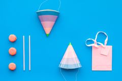 Birthday party accessories. Party hat, sweets, paper bag for gift on blue background top view copy space pattern.  Stock Photos