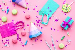 Birthday party accessories. Party hat, sweets, paper bag for gift on pink background top view copy space pattern.  Royalty Free Stock Photography