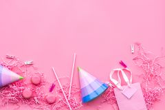 Birthday party accessories. Party hat, sweets, paper bag for gift on pink background top view copy space pattern.  Royalty Free Stock Photos