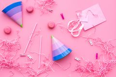 Birthday party accessories. Party hat, sweets, paper bag for gift on pink background top view copy space pattern.  Royalty Free Stock Image